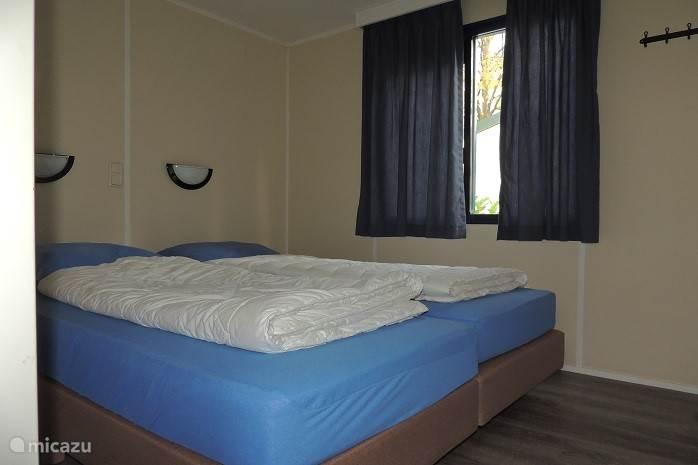 Slaapkamer met boxspring bedden en een ruime hang legkast