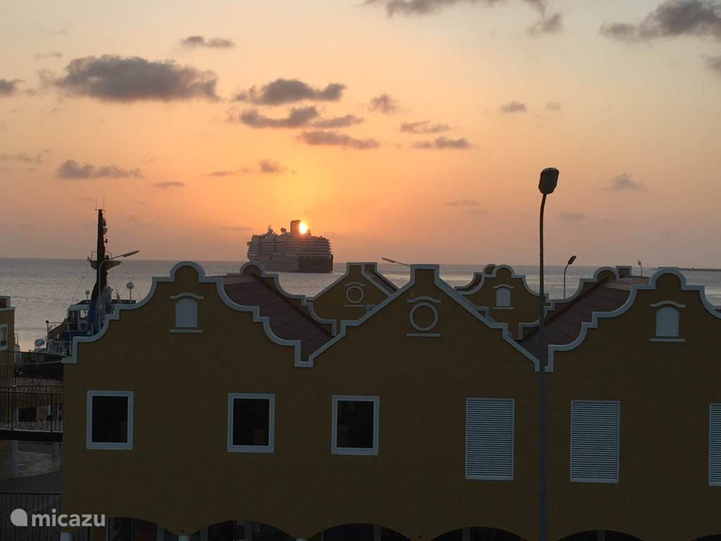 Vanaf het balkon, vertrekkend cruiseschip met ondergaande zon