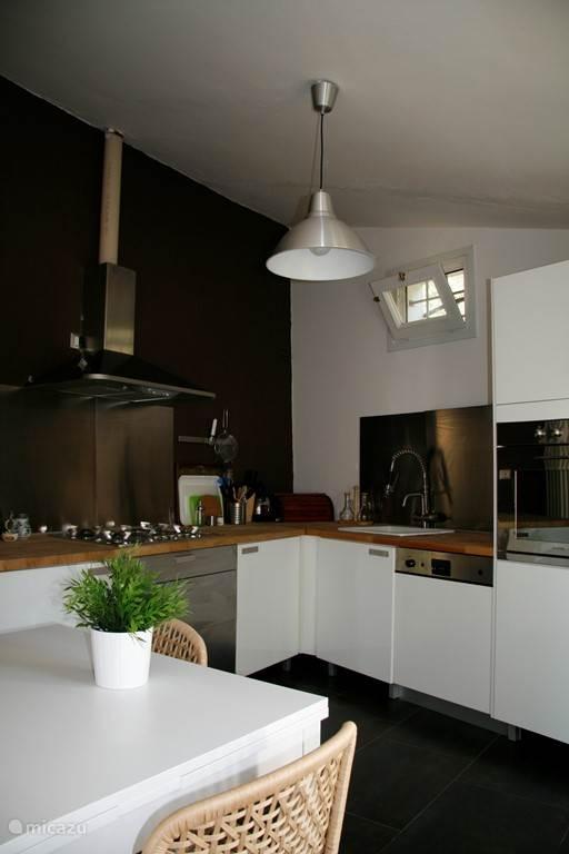 de moderne lichte keuken, met openslaande deuren naar het terras