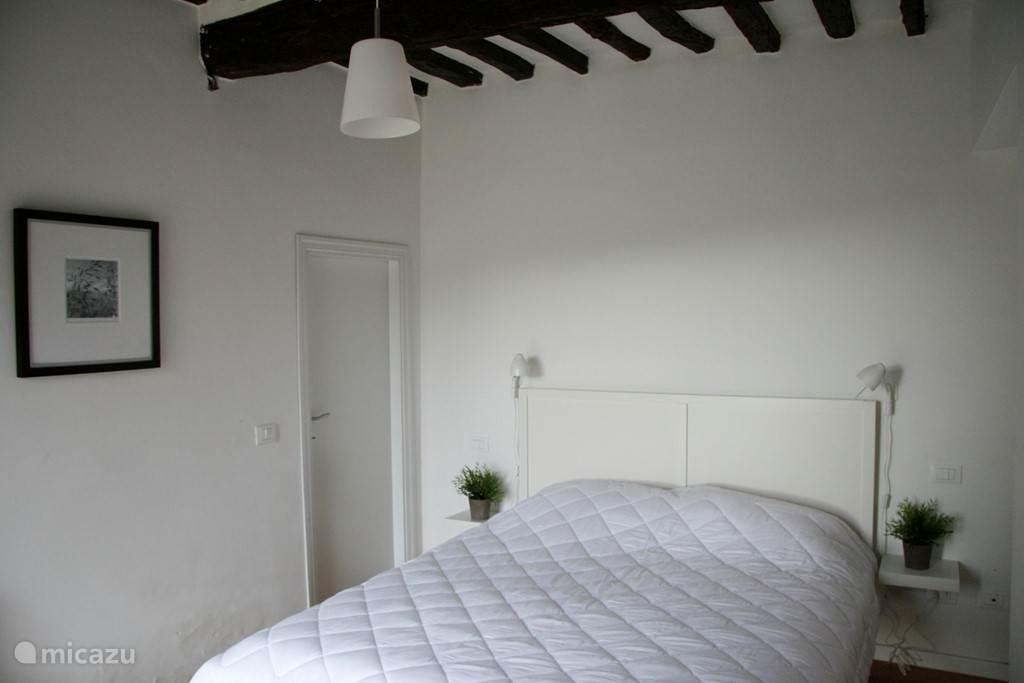 Lichte tweepersoons slaapkamer met vaste kast en openslaande deuren naar tuin/zwembad