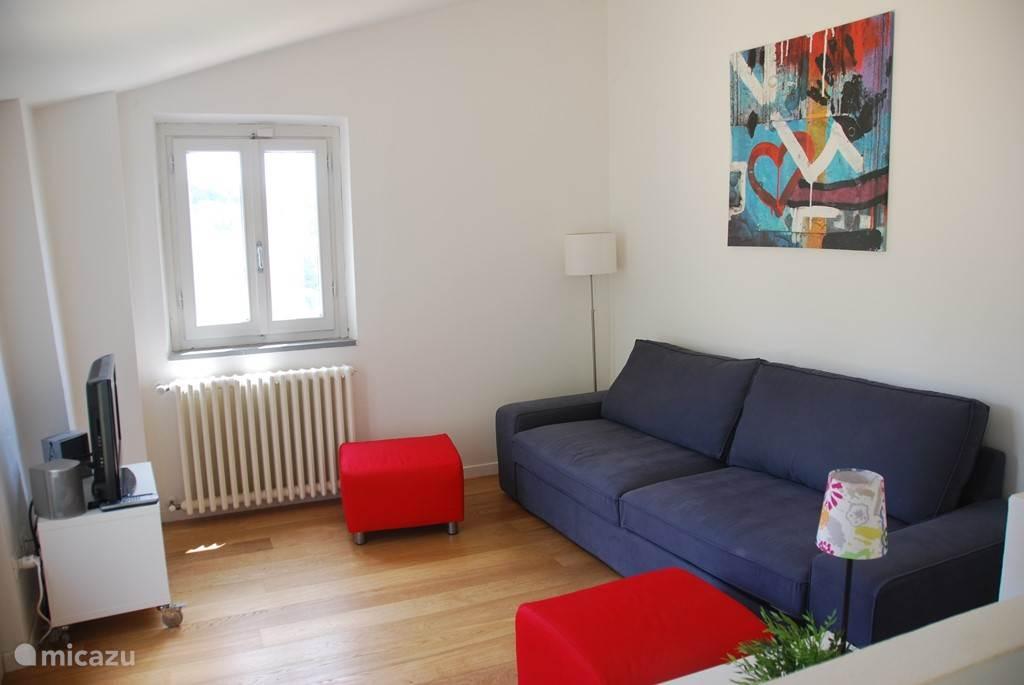 De lichte woonkamer voorzien van slaapbank met openslaande deuren naar het terras en fijn uitzicht op de tuin en het zwembad