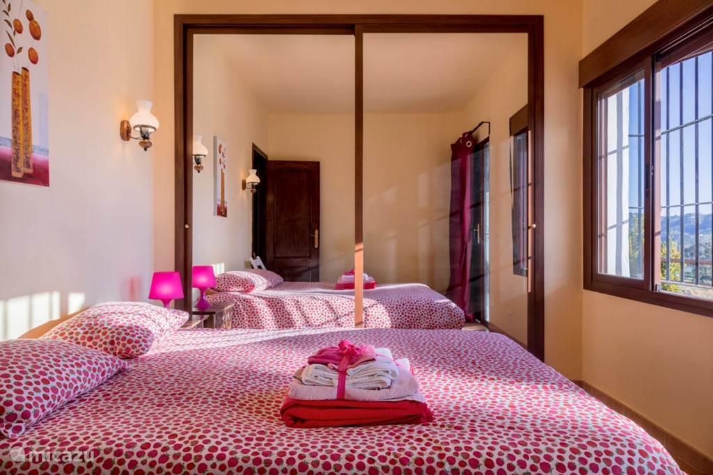 De slaapkamer met het tweepersoonsbed en de grote kast met spiegeldeur met genoeg kleerhangers en planken voor al uw kleding.