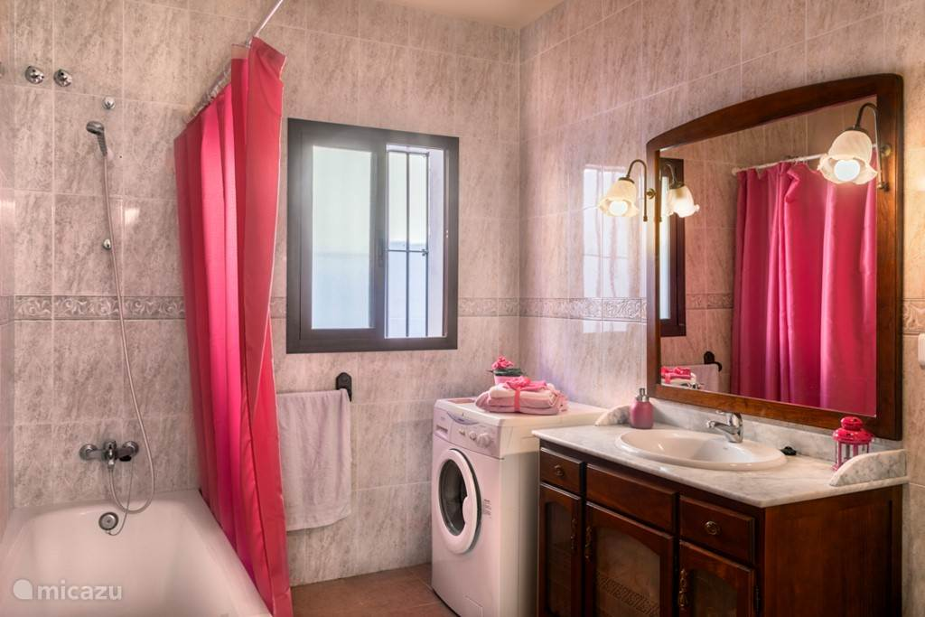 Onze roze badkamer met het bad en daarin de douche, de wastafel en de wasmachine. U vindt hier ook de wc.