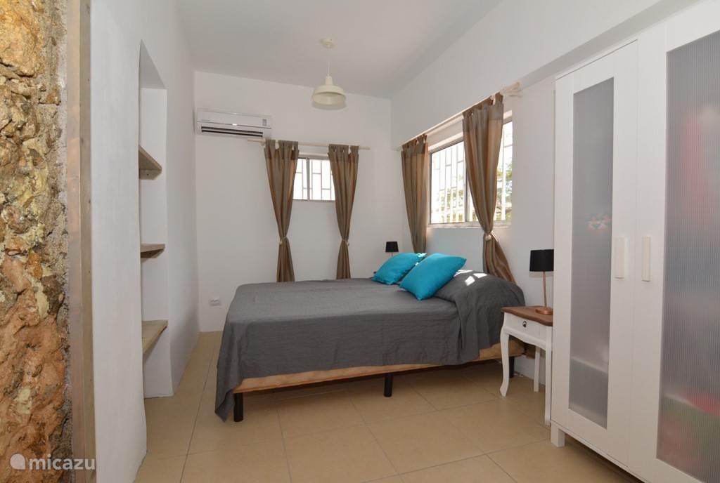 De hoofdslaapkamer met aan de linkerkant een schilderij van de oude bouwstijl op Bonaire
