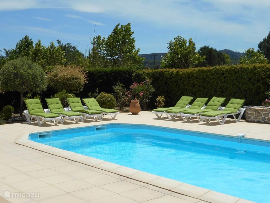 rond het zwembad ligt een groot terras met 8 ligstoelen