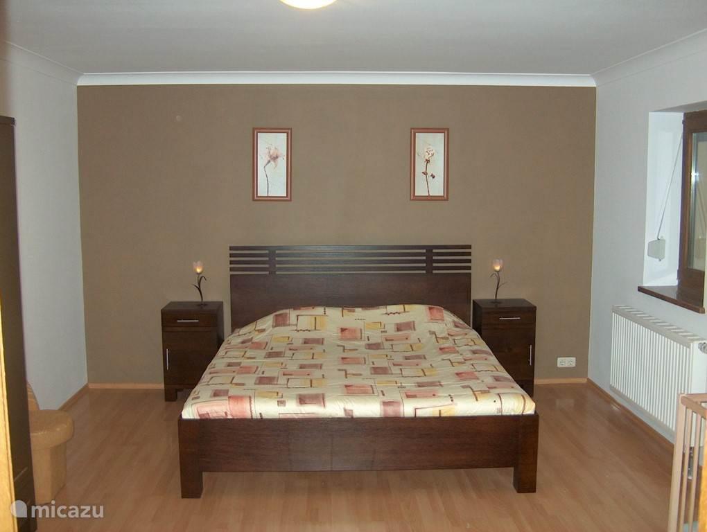 Slaapkamer op de begane grond. Deze slaapkamer heeft een eigen badkamer, waar naast een wastafel, douche, toilet en bidet ook de wasmachine geplaatst is.