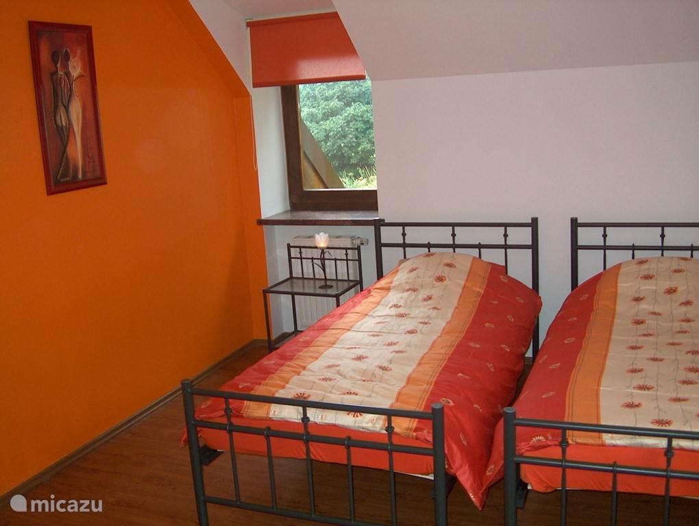 Wanneer u boven komt, treft u gelijk rechts bij de trap deze oranje kamer met 2 eenpersoons bedden.