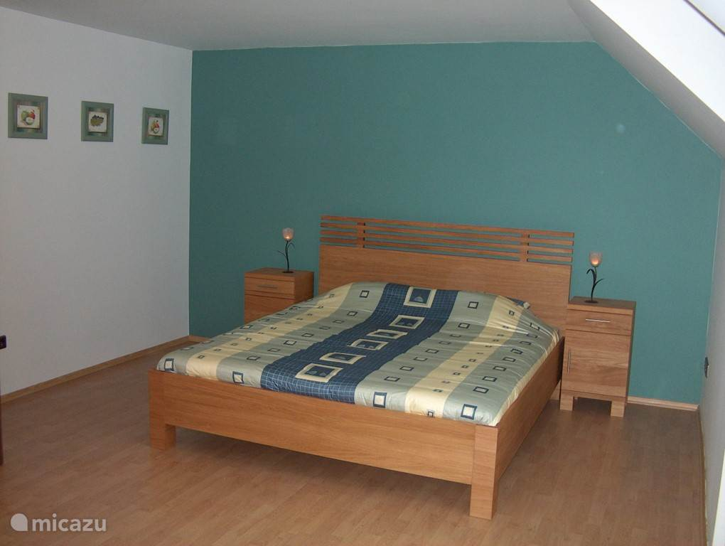 In het midden van de woning, aan de achterzijde op de eerste verdieping deze rustgevend groene slaapkamer met tweepersoonsbed. Op deze kamer staat vaak ook een babybedje, commode en aankleedkussen.
