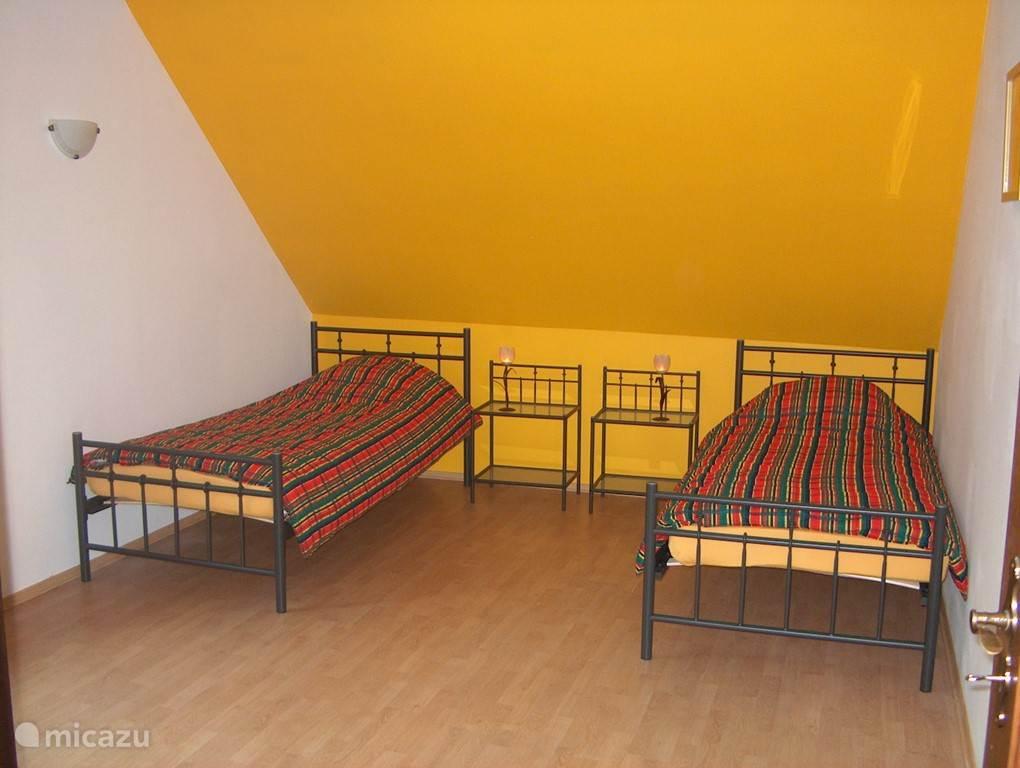 Aan de achterzijde van het huis, boven de garage ligt deze slaapkamer met twee 1-persoonsbedden en een tweepersoons slaapbank.