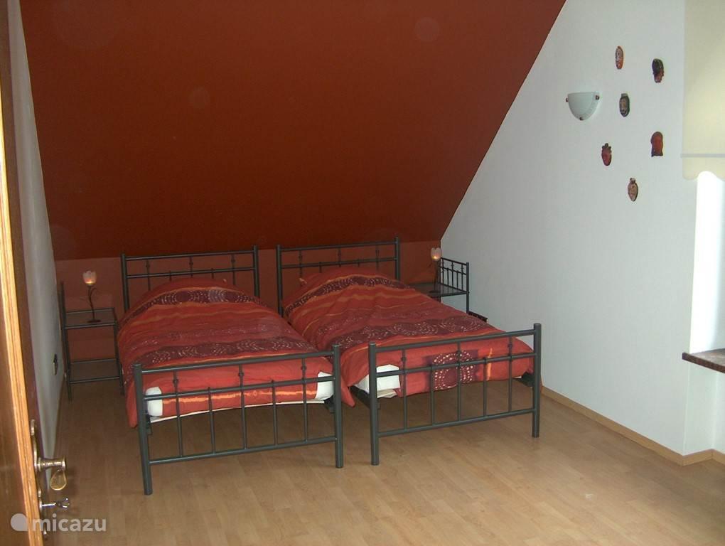 Ook boven de garage, aan de voorzijde van de woning vindt u deze chocolade-bruine slaapkamer met twee 1-persoonsbedden.