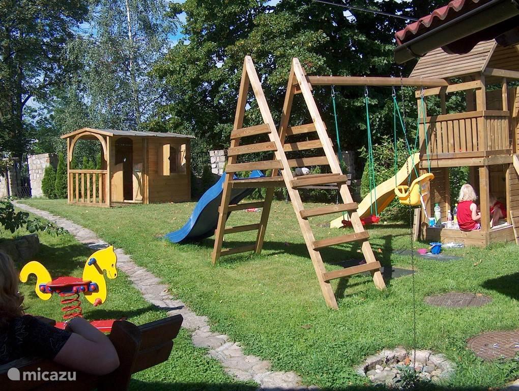 Voor onze kleine gasten een heerlijk plekje in de tuin om te spelen in het speelhuisje, glijbanen, schommelen, zandbak of op de wipkip.