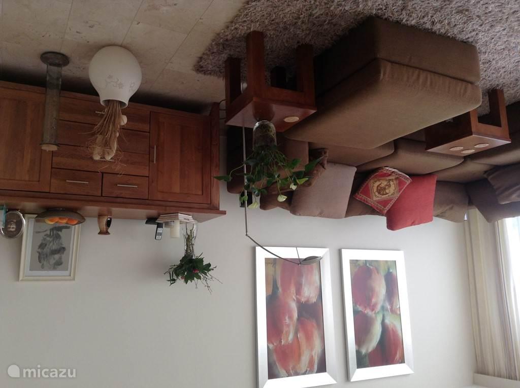 De woonkamer is zeer ruim met comfortabele hoekbank, leunstoel uitkijkend op duin