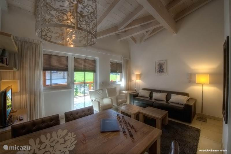 Kaprun Mountain Resort TopE21 living room with beautiful high ceilings and stylishly furnished.