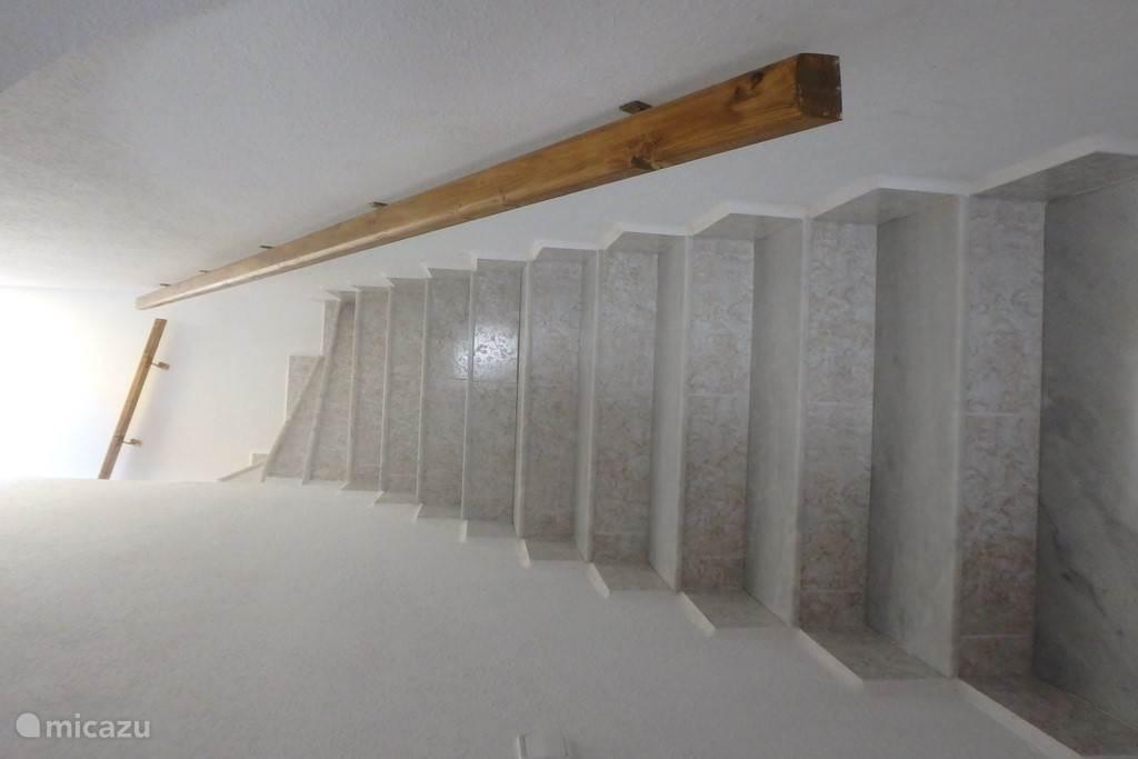 Trap vanuit de woonkamer naar bovenverdieping met slaapkamer, badkamer en dakterras.