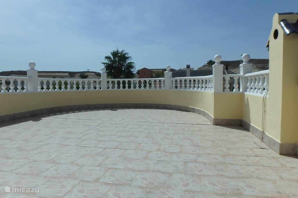 Dakterras met uitzicht op terras met privé zwembad en in de ongerepte natuur en bergen.