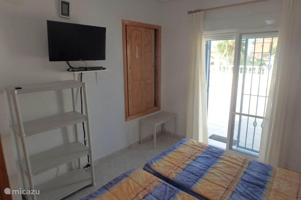 Slaapkamer boven met airco, plafondventilator, Sat TV, verwarming en toegang naar badkamer en dakterras.