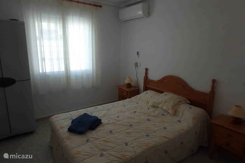 Slaapkamer (kleinere) beneden. Met airco, verwarming en uitzicht op het terras en zwembad. Gelegen tegenover badkamer en grotere slaapkamer.