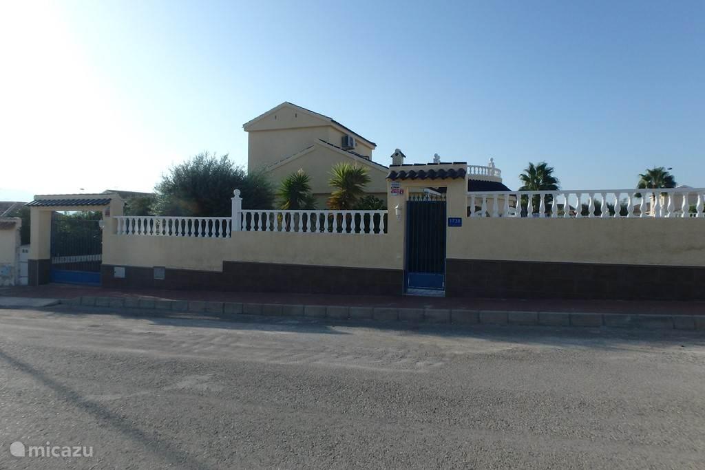 Casa Mazarron gezien vanaf de straatkant. Grondstuk is geheel voorzien van muren rondom en 2 afsluitbare poorten aan de voorkant.