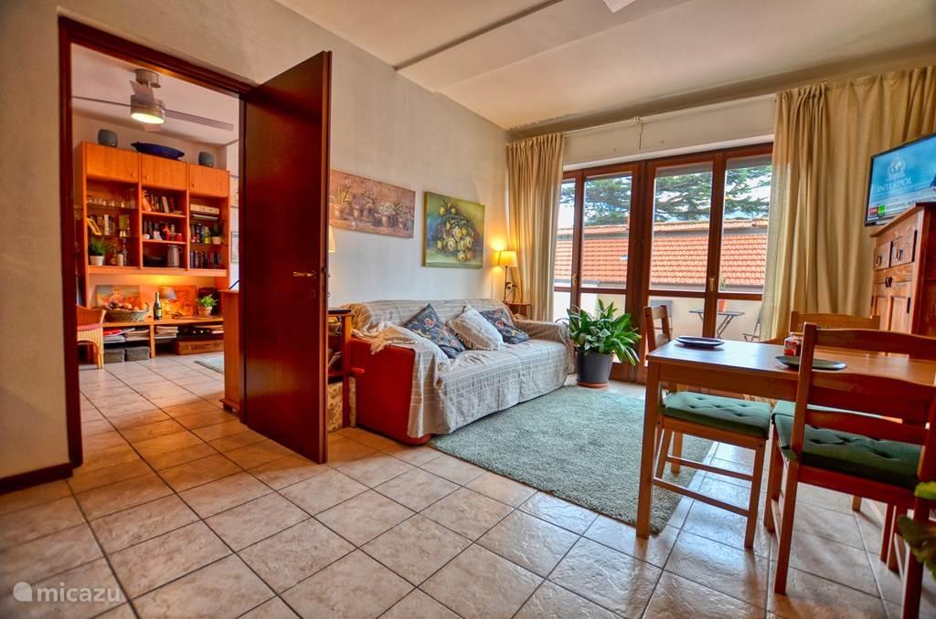 De eerste woonkamer met aansluitend het ruime balkon met elektrische zonneluifel en tuinmeubilair.