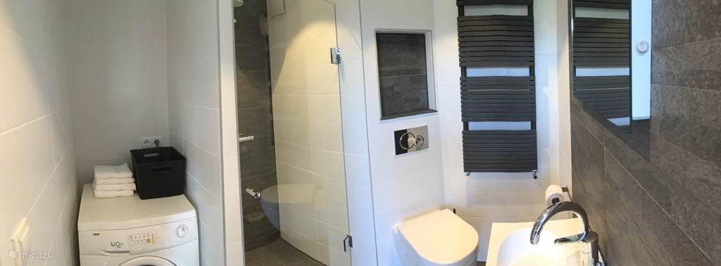 Badkamer met wasmachine en regendouche bevind zich op de begane grond.