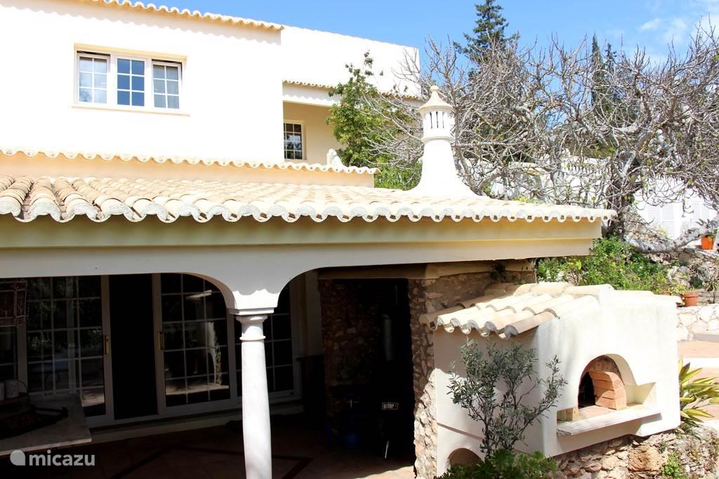 Aanzicht van de grote veranda met BBQ en zicht op de villa.