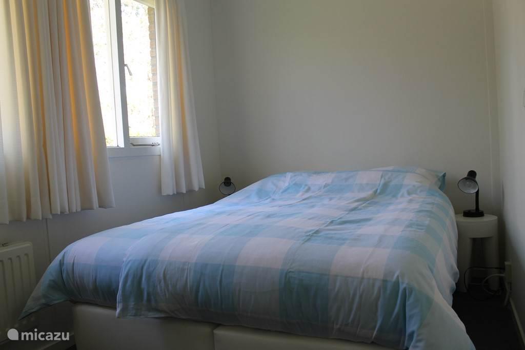Slaapkamer met een tweepersoonsbed en kast.