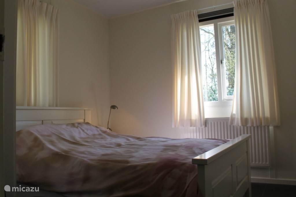 Slaapkamer met tweepersoonsbed en kast.