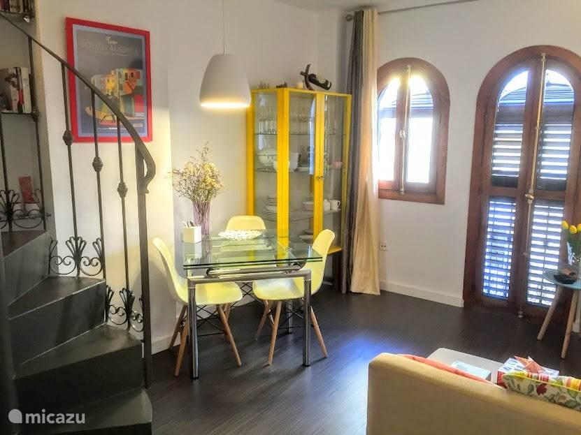 Huiskamer met eettafel en de wenteltrap naar de bovenverdieping