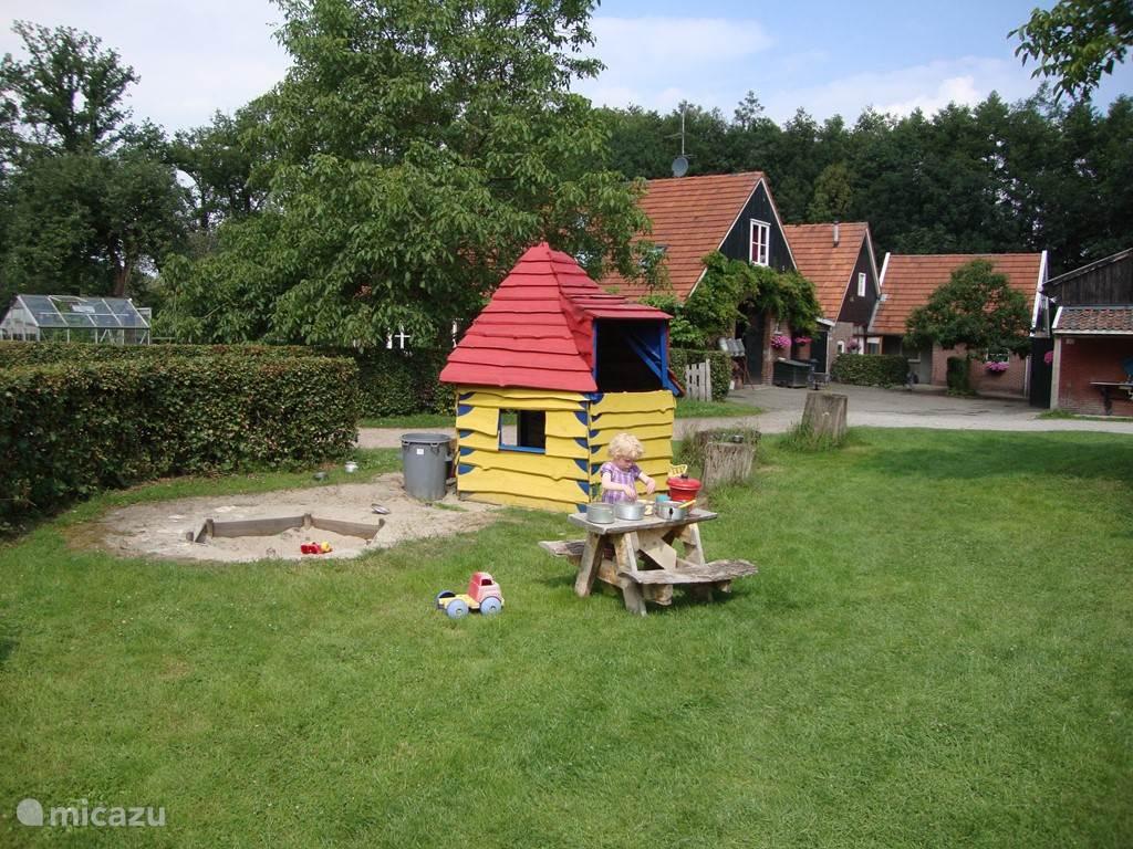 Erf van het Diekshoes met speeltuintje voor de kinderen. (zandbak, speelhuisje, schommel, skelters, step, fietsjes, ´s zomers wordt een badje opgezet)
