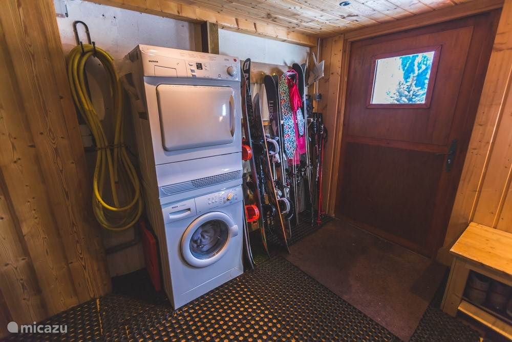 Downstairs storage room with ski racks, washer and dryer