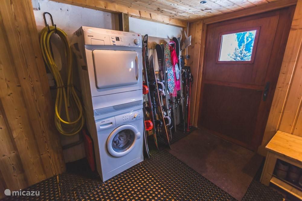 Beneden berging met skirekken, wasmachine en droger