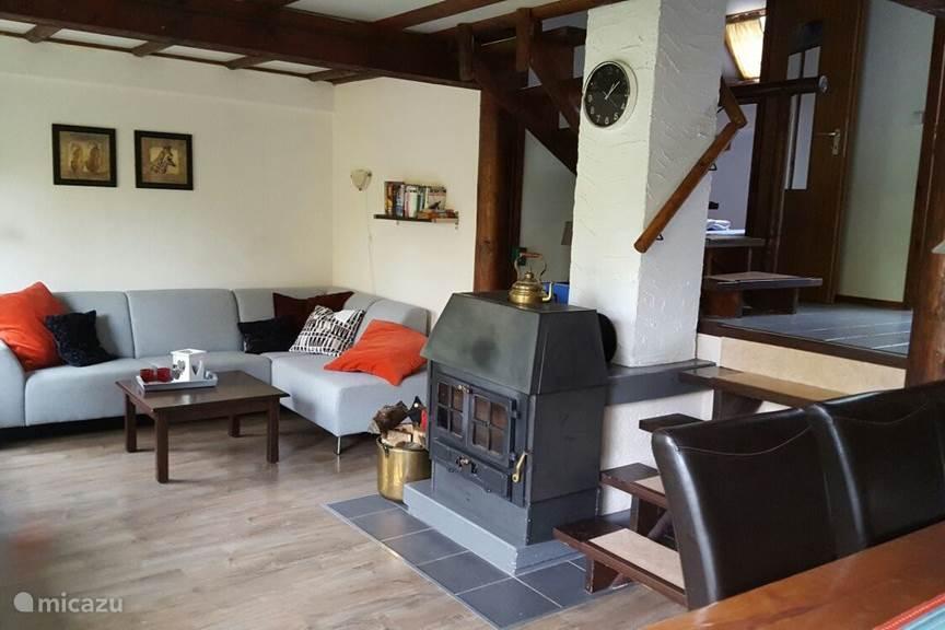 Gezellige woonkamer met comfortabele bank en houtkachel