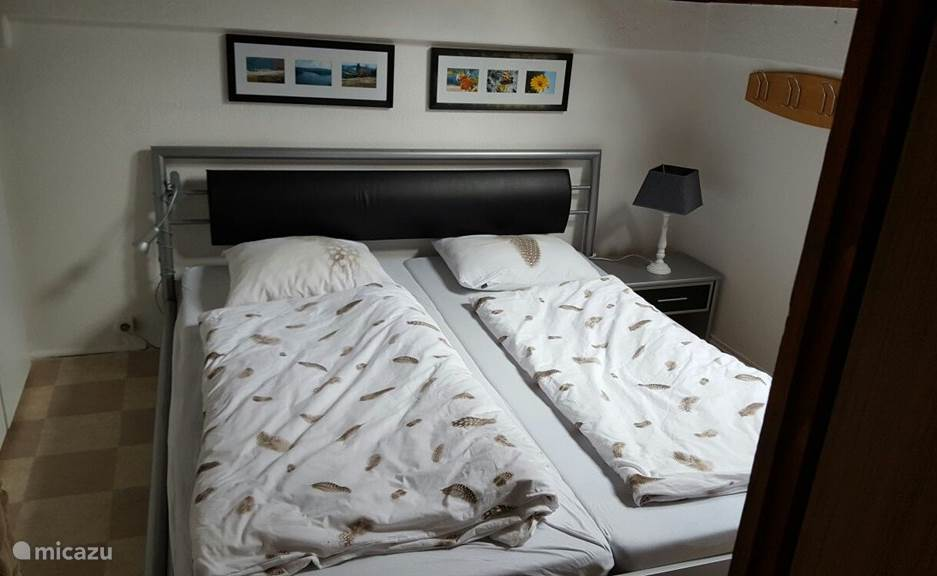 Slaapkamer 1: Modern tweepersoonsbed en apart toilet met wastafel