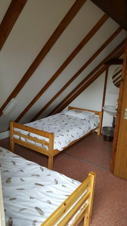 Bedroom 2 with two single beds with private sink and patio door to balcony
