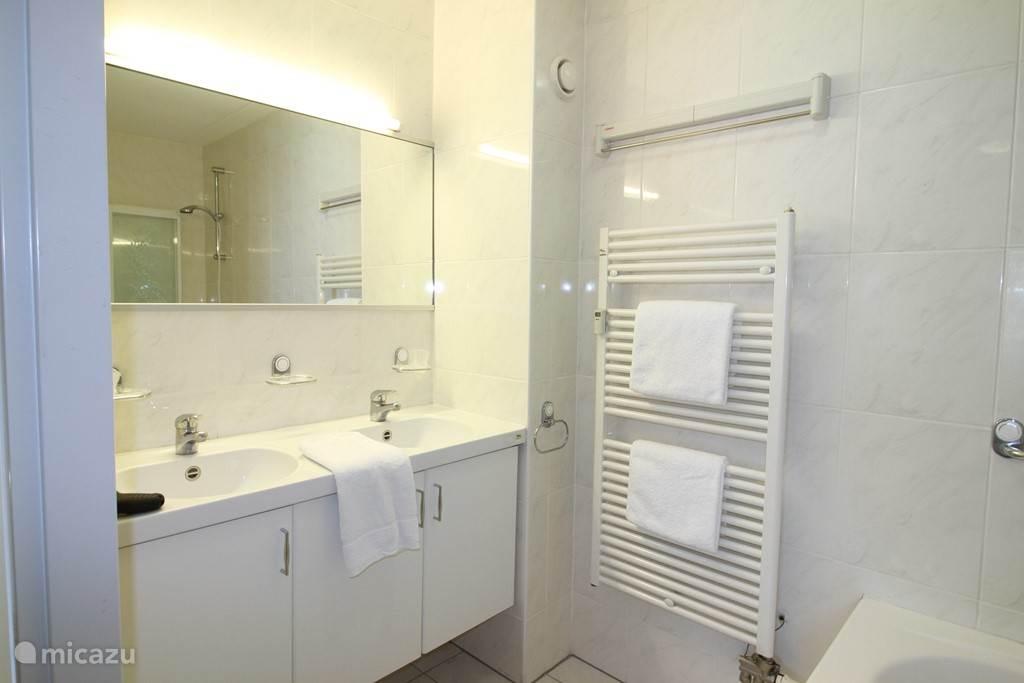 De badkamer met dubbele wasbak  en bubbelbad met een douche en toilet