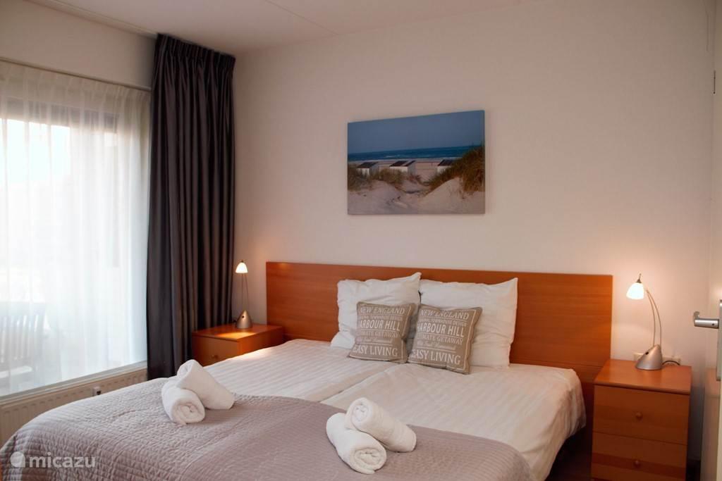 Slaapkamer met twee boxspring bedden dekbedden en kussens met ensuite badkamer