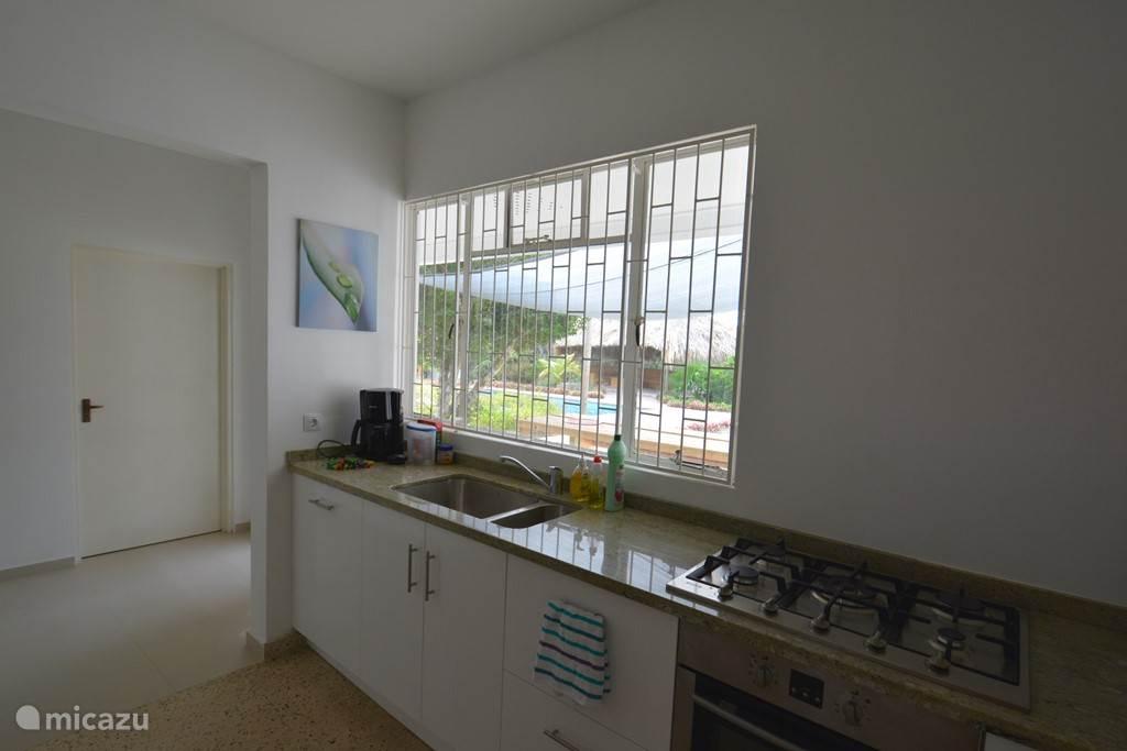 Terwijl je aan het koken bent, kijk je uit over het zwembad en het terras aan de achterzijde van de villa!