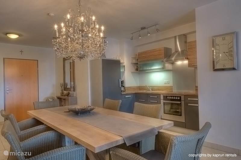 Het appartement bestaat uit een ruime living met open keuken, een grote eettafel en een gezellige zithoek met open haard, waar het heerlijk genieten is na een dag in de bergen. Vanuit de zithoek heeft u een panoramisch uitzicht over het dorp en de bergen.