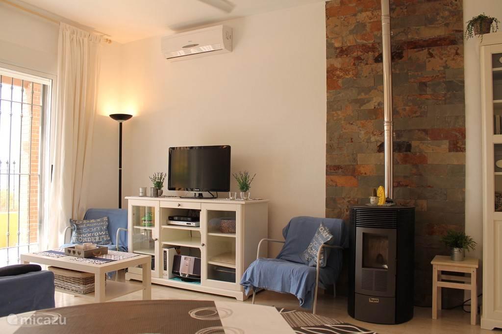 Woonkamer met airco, pelletkachel, tv, wii, stereo installatie