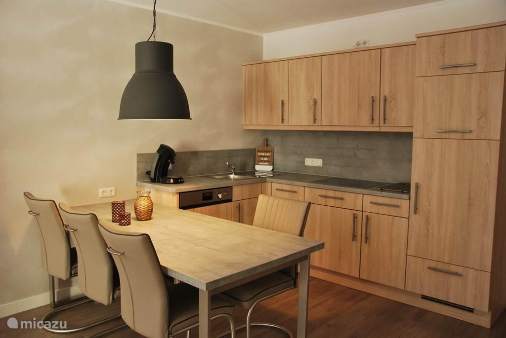 De keuken met vaatwasser, keramische kookplaat, koelkast en magnetron.
