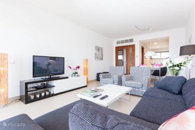 De woonkamer met hoekbank en  fauteuil. De schuifpui opent zich vrijwel geheel naar het terras, dat u zodoende bij de woonkamer kunt betrekken.