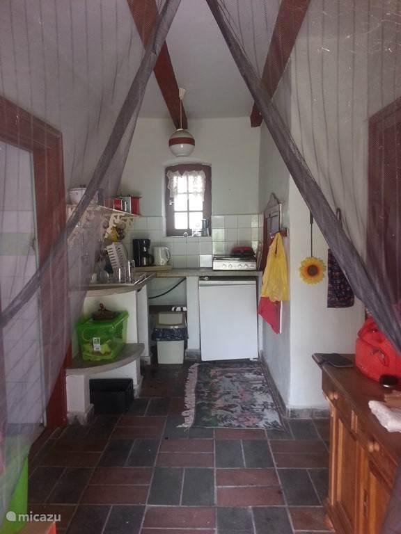 In de keuken staat een koelkast, 4 pits fornuis. Alles is aanwezig om er te kunnen koken, ook pannen, borden en bestek e.d.
