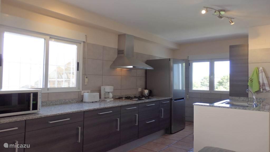 Ruime moderne open keuken van alle gemakken voorzien