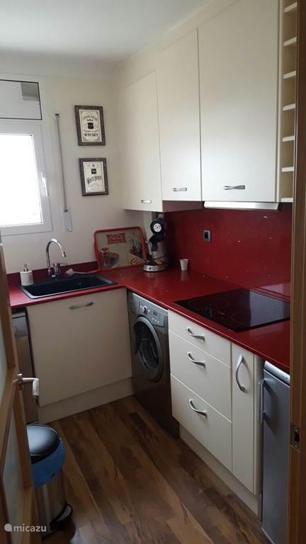 De mooie keuken met wasmachine, vaatwasser, koelkast en magnetron.