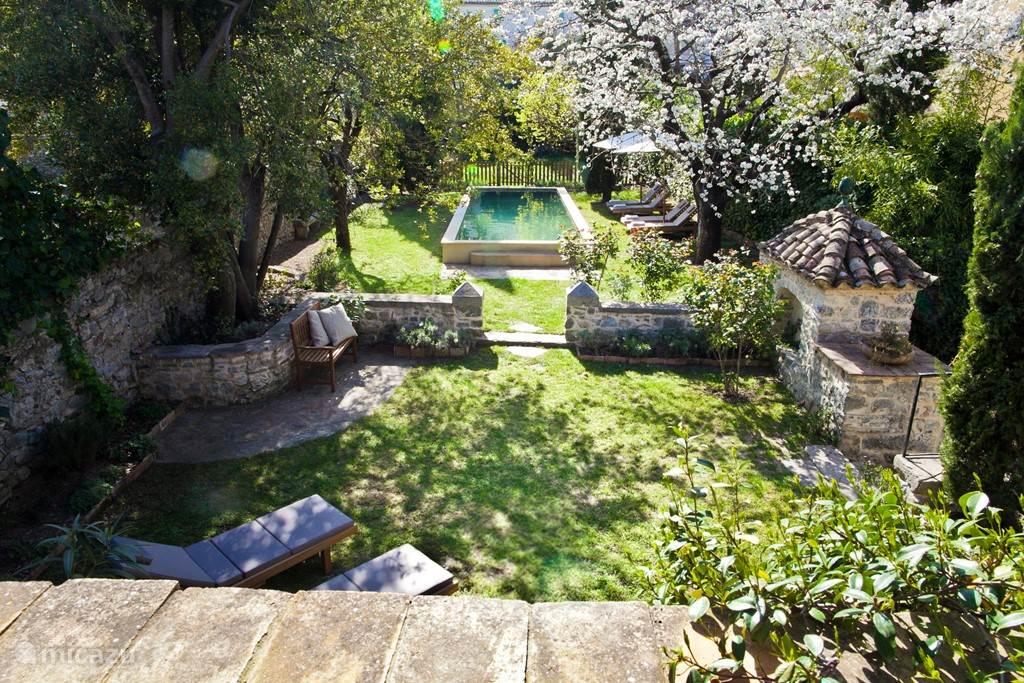 Uitzicht naar zwembad en tuin vanaf de veranda