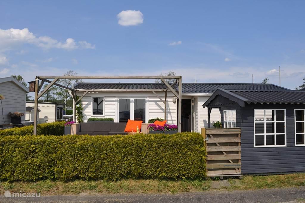 Mooi strak buiten terras met handig ruim bemeten tuinhuisje met zithoek.