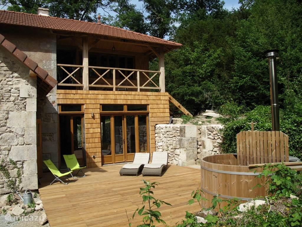 Terrace with woodburning hot tub overlooking our lake. The garden goes on in the forest