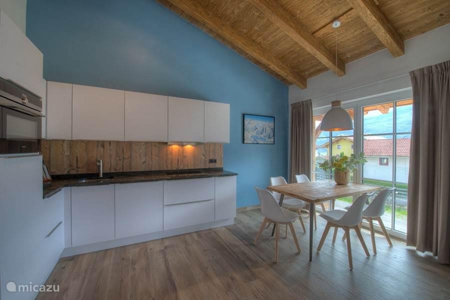 Vanaf deze kant kunt u goed zien hoe  iedereen samen kan genieten in deze kamer. Terwijl de kok van het gezelschap zijn of haar kookkunsten demonstreert, kunnen de andere mensen toekijken onder het genot van een glas zijn op de bank of aan de eettafel.