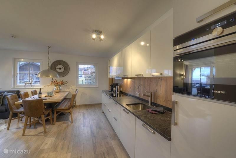 Koken en eten is ook een genot in dit penthouse appartement! Een ruime, moderne, keuken met grote eettafel!