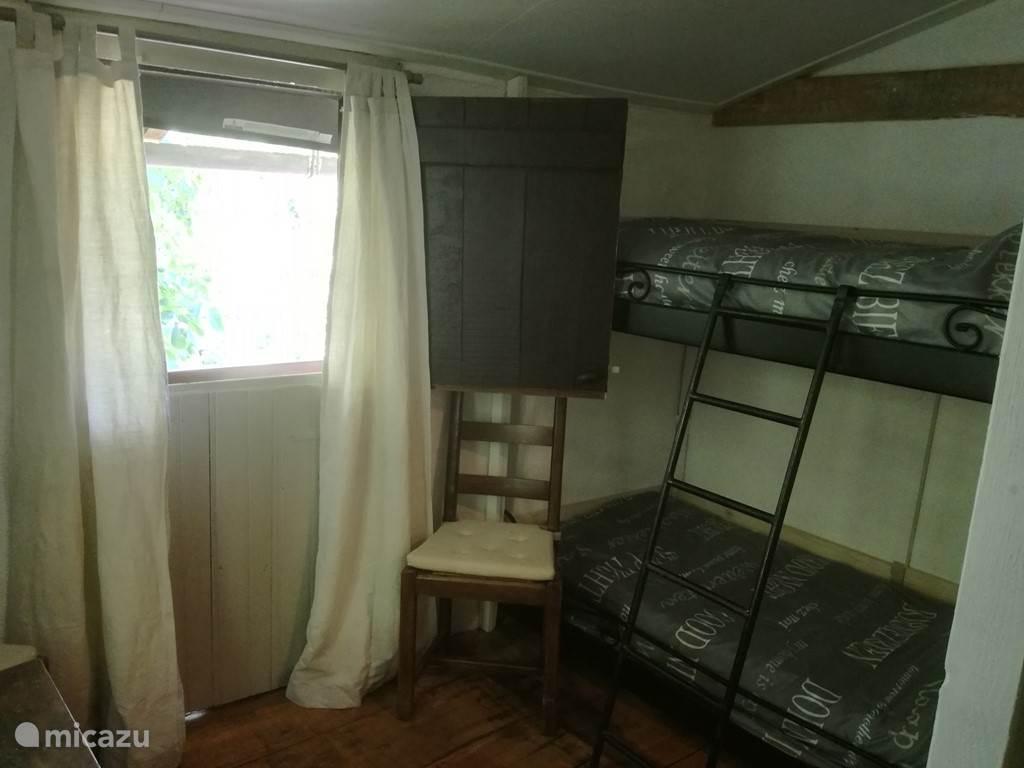 De tweede slaapkamer met een stapelbed en uitzicht op de prachtige notenboom. Je waant je in een boomhut.